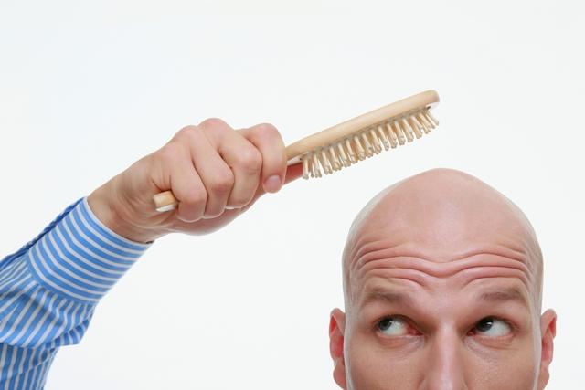 bald man holdinga hair brush to his head